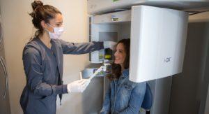 Teen patient sitting in ICAT dental imaging machine