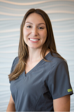 Smiling Trailside Dentistry team member in grey dental scrubs